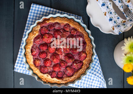 Open cake with strawberries in blue bowl for breakfast, on a black wooden background. Homemade baking. Free space for text. Copy space . Flat lay. - Stock Photo