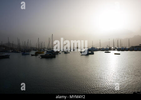 MINDELO, CAPE VERDE - DECEMBER 07, 2015: Boats and yachts in port of Sao Vicente island in bright light of the misty sunset