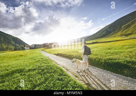 Tourist with dog in countryside. Young man walking with labrador retriever on dirt road against sunset. South Tyrol, Italy - Stock Photo