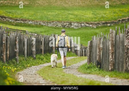 Tourist with dog in countryside. Young man walking with labrador retriever on dirt road. - Stock Photo