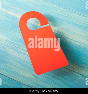 Red door hanger on a blue wooden planks - Stock Photo