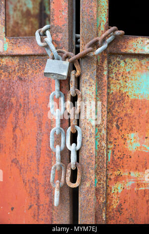 Chained and padlocked metal doors with rusty red paintwork - Stock Photo