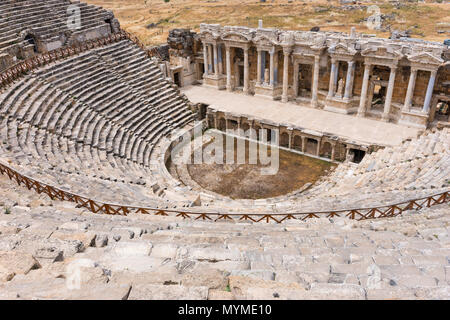 The ancient stone theatre and Greek amphitheatre in Hierapolis near Pamukkale in Turkey now a UNESCO World Heritage Site viewed looking down from the  - Stock Photo