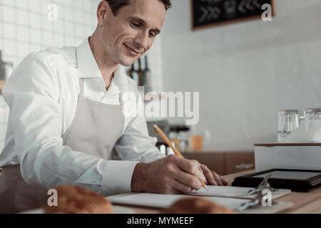 Close up of pleased man that making notes - Stock Photo