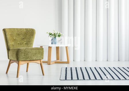 Green armchair in white living room interior with empty wall - Stock Photo