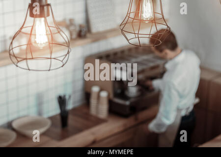 Competent barista making coffee for client - Stock Photo