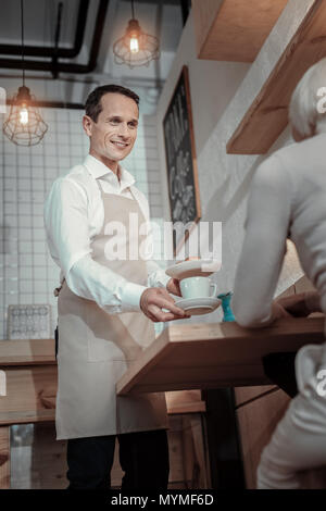 Handsome waiter communicating with his client - Stock Photo
