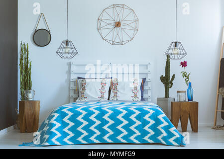 Bedroom with industrial accessories, copper clock, lamps in ethnic style - Stock Photo