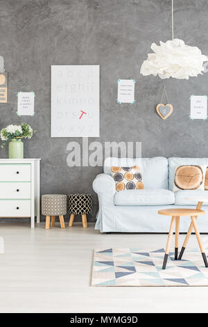 Grey living rooom with sofa, dresser and upholstered stools - Stock Photo