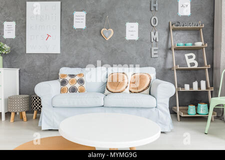 Living room with comfortable sofa, round table and simple regale - Stock Photo