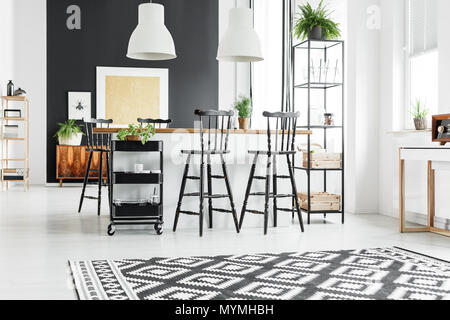 Black and white geometric carpet in rustic kitchen with bar stools at wooden countertop - Stock Photo
