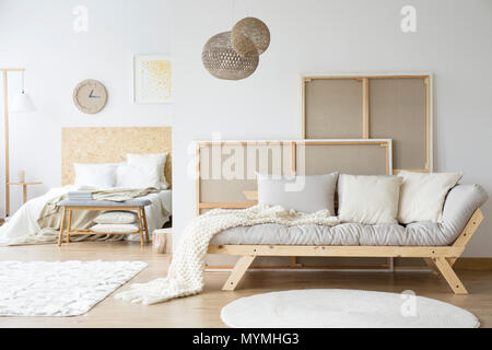 Kings-size bed and a cozy sofa in a monochromatic white room interior - Stock Photo