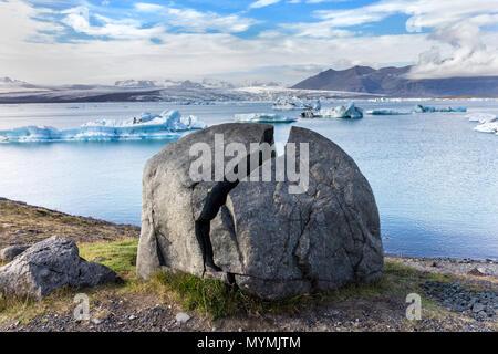 Split Rock and Icebergs Floating in the Jokulsarlon Glacial Lagoon Vatnajökull National Park Iceland - Stock Photo