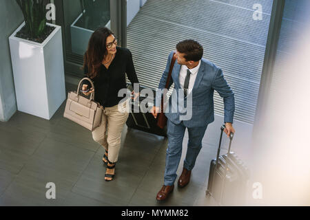 Businessman and woman walking together with baggage and talking. Business people arriving for conference. - Stock Photo