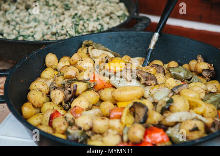 Preparation of vegetable dish from mushrooms and vegetables in a frying pan - Stock Photo