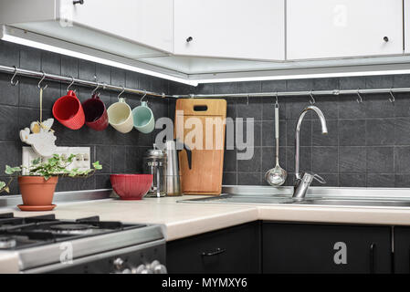 A fragment of the modern style kitchen with rail system and kitchen utensils and houseplant - Stock Photo
