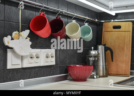 A fragment of the modern style kitchen with rail system and tea cups closeup - Stock Photo