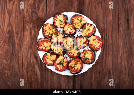Dish of fried slices of eggplant, tomatoes and sprinkle with cheese and dill in a bowl on a wooden background - Stock Photo