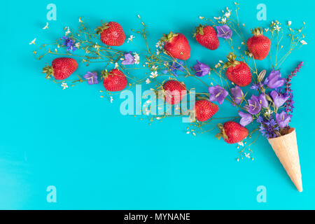 Waffle cone with wild strawberry and blue bells and white flowers blossom bouquets on blue surface. Flat lay, top view sweet food floral background. - Stock Photo