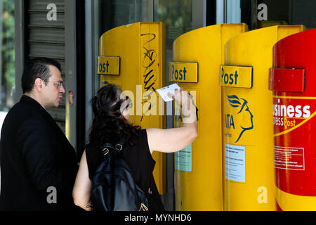 Woman posting a letter outside a Post office in Athens Greece - Stock Photo