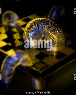slinky on checkerboard - Stock Photo