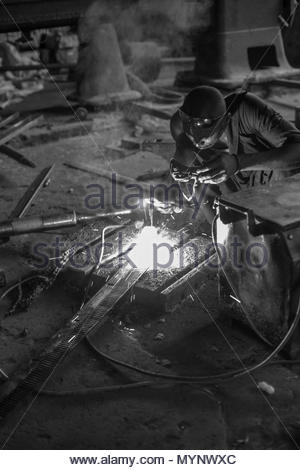 African man welding in a factory - Stock Photo