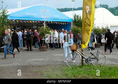 Hay Festival entrance with bicycle, banner and visitors outside, woman looking at programme Saturday evening 26 May 2018 Hay-on-Wye UK  KATHY DEWITT - Stock Photo
