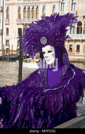 Campo della Salute, Dorsoduro, Venice, Italy: carnevale reveller wearing feathered costume in deep purple, posing by the Grand Canal - Stock Photo