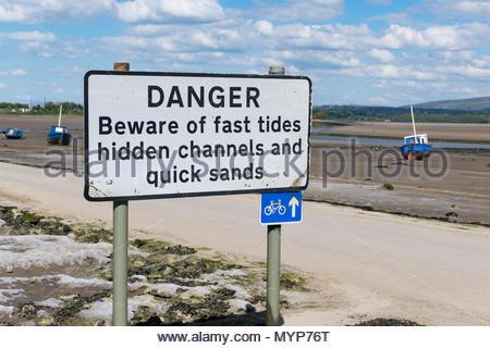 Sign warning of Danger of Fast Tides, hidden channels and quick sands at Sunderland Point near Lancaster, UK - Stock Photo