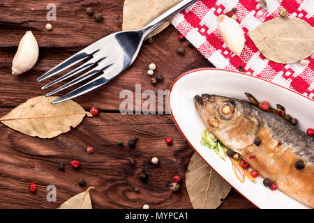 Small fried fish Baltic herring in a bowl on a table with spices top view - Stock Photo