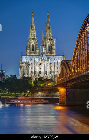 The famous Cologne Cathedral and the Hohenzollern railway bridge at dusk - Stock Photo