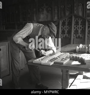 1950s, historical picture showing an elderly male craftsman or woodworker inside a workshop using a hammer and chisel to carve out intricate patterns on a rectangular piece of softwood, England, UK. - Stock Photo