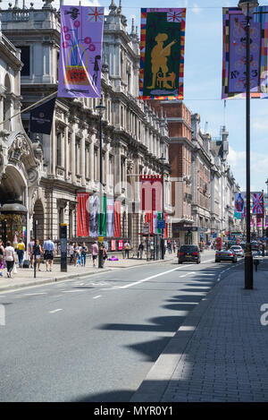 In a street busy with people colourful banners hang above the road in Piccadilly. Advertising banners hang outside Royal Academy, Burlington House - Stock Photo