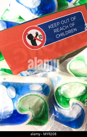 Colorful laundry detergent pods with 'keep out of reach of children' warning, USA - Stock Photo