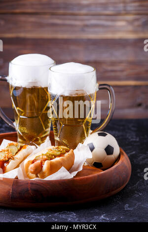 Image of two mugs of beer and hot dogs on wooden tray with football - Stock Photo