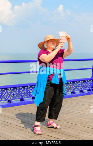 Middle aged woman taking a selfie on eastbourne pier - Stock Photo