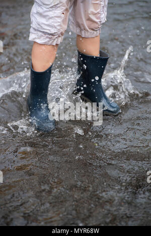 Young Boy Wearing Rain Boots Walks Through A Puddle Of