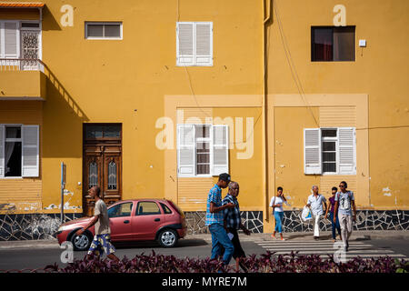 Life in Mindelo, residents walking the streets. Town architecture,  large yellow building wall MINDELO, CAPE VERDE - DECEMBER 07, 2015