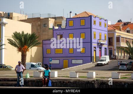 Vibrant violet building. Colorful architecture of Mindelo Town. People waiting for a transport MINDELO, CAPE VERDE - DECEMBER 07, 2015