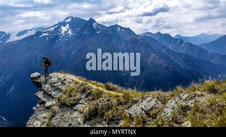 traveler standing on the edge of a cliff. cascade saddle, New Zealand - Stock Photo