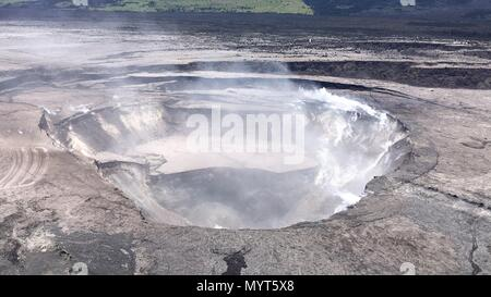 Hawaii, USA. 6th June, 2018. Aerial view of the Halemaumau crater showing collapse of the crater walls enlarging the caldera and deflating the lava lake which once filled the space caused by the eruption of the Kilauea volcano June 6, 2018 in Hawaii. The recent eruption continues destroying homes, forcing evacuations and spewing lava and poison gas on the Big Island of Hawaii. Credit: Planetpix/Alamy Live News - Stock Photo