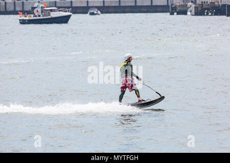 Poole, Dorset, UK. 8th June 2018. The 1st day of the 3 day extravaganza - the 4th annual Poole Harbour Boat Show, the biggest free to attend boat show on the South Coast. After a cloudy start to the day, the sun comes out and weather improves for the afternoon for visitors to enjoy the show. 57 year old rider thrills the crowd with new jetsurf, jet surf, reaching top speed of 37mph, a motorised surf board. Credit: Carolyn Jenkins/Alamy Live News - Stock Photo