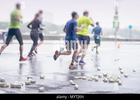 Group of runners on marathon at service point. Pile of used disposable white cardboard cups for beverages, selectiv focus, blur - Stock Photo