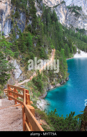 Visitors  can walk around Lake Braies (Pragser Wildsee, Lago di Braies) on a hiking trail that runs along lakeshore - Stock Photo