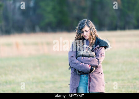 Young sad woman girl walking with head eyes closed down holding hugging purse in winter coat, unhappy stomach ache pain - Stock Photo