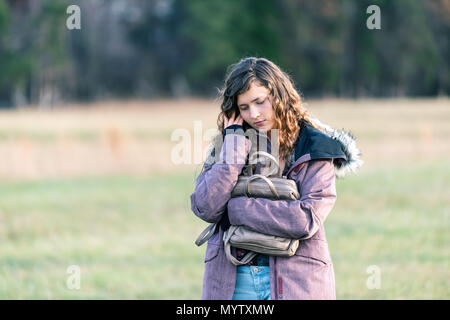 Young unhappy woman girl walking with head eyes closed down holding hugging purse in winter coat, sad stomach ache pain - Stock Photo