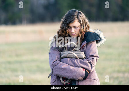 Young sad woman girl walking with eyes closed down holding hugging purse in winter coat, unhappy stomach ache pain - Stock Photo