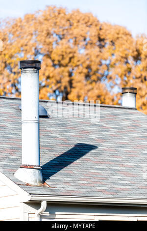 Vertical closeup of house shingles rooftop roof with chimney, autumn orange yellow golden foliage leaves on tree in background - Stock Photo