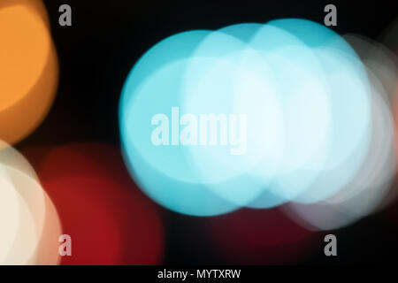 Abstract closeup of colorful blue large bokeh circles in traffic dark night evening colors, street lights background - Stock Photo