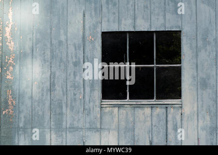 Window in a Blue Wall with Chipped and Pealing Paint - Stock Photo